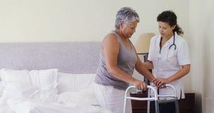 Medico femminile che aiuta donna senior a camminare con il camminatore 4k archivi video