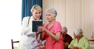 Medico femminile che assiste donna senior sulla compressa digitale stock footage