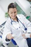Medico femminile che benda polso storto mano maschio immagine stock