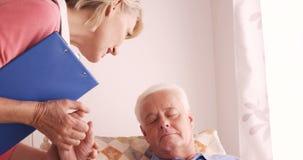 Medico femminile che consola ad un paziente senior archivi video