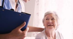 Medico femminile che consola ad una donna senior stock footage