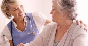 Medico femminile che consola ad una donna senior video d archivio