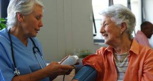Medico femminile che controlla pressione sanguigna della donna senior 4k archivi video