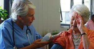 Medico femminile che controlla pressione sanguigna della donna senior 4k video d archivio