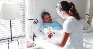 Medico femminile che controlla pressione sanguigna di un uomo senior 4k archivi video