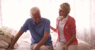 Medico femminile che controlla un uomo senior con lo stetoscopio video d archivio