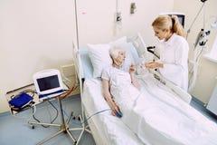 Medico femminile che dà le pillole al paziente pensionato immagini stock