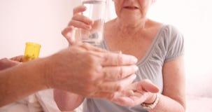 Medico femminile che dà medicina alla donna senior video d archivio