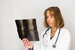 Medico femminile che esamina la foto dei raggi x Immagini Stock