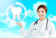 medico femminile che indica l'icona del dente di salute immagini stock