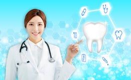 medico femminile che indica l'icona del dente di salute fotografia stock libera da diritti