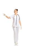 Medico femminile che indica a sinistra Fotografia Stock