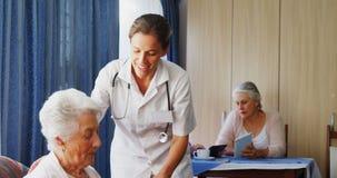 Medico femminile che interagisce con la donna senior 4k video d archivio