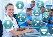Medico femminile che lavora al computer portatile con le icone mediche di esagono dell'interfaccia fotografia stock libera da diritti