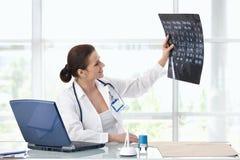 Medico femminile che lavora allo scrittorio fotografie stock