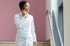 Medico femminile che parla su un telefono cellulare immagini stock libere da diritti