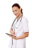 Medico femminile che per mezzo del calcolatore del ridurre in pani. Immagini Stock