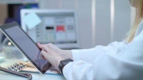 Medico femminile che per mezzo della compressa nel luogo di lavoro medico Infermiere che per mezzo del pc della compressa video d archivio