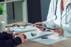 Medico femminile che presenta l'esame medico risulta al paziente che usando la t immagine stock libera da diritti