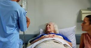 Medico femminile che regola il gocciolamento del dispositivo di venipunzione nel reparto 4k archivi video
