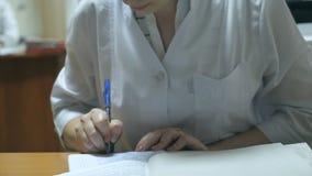 Medico femminile che scrive una prescrizione in un ospedale I giovani curano il lavoro alla scrivania e la scrittura delle cartel archivi video