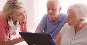 Medico femminile che si consulta ad una coppia senior video d archivio