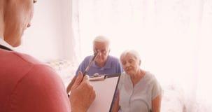 Medico femminile che si consulta ad una coppia senior e che redige una perizia medica stock footage