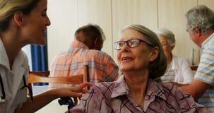 Medico femminile che si inginocchia mentre parlando con donna senior disabile sulla sedia a rotelle 4k archivi video