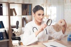 Medico femminile che si siede allo scrittorio in ufficio con il microscopio e lo stetoscopio La donna sta esaminando la ciambella immagine stock