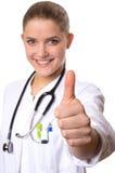 Medico femminile che sorride, pollici su Fotografia Stock