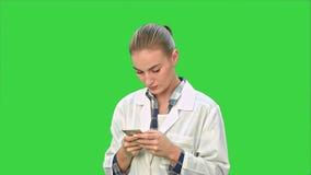 Medico femminile che usando i messaggi mandanti un sms facendo uso dello smartphone moderno e sorridendo su uno schermo verde, ch video d archivio