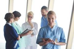 Medico femminile con il computer della compressa che sta davanti al gruppo Immagini Stock