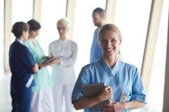 Medico femminile con il computer della compressa che sta davanti al gruppo Fotografia Stock