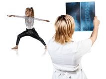 Medico femminile considera i raggi x della bambina nella posa di yoga Fotografie Stock