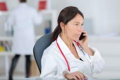 Medico femminile del ritratto sul telefono in ufficio Fotografie Stock Libere da Diritti