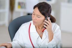 Medico femminile del ritratto sul telefono in ufficio Immagini Stock Libere da Diritti