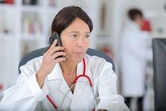 Medico femminile del ritratto sul telefono in ufficio Immagini Stock