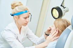 Medico femminile della gola OTORINOLARINGOIATRICA del naso dell'orecchio al naso d'esame della ragazza del lavoro immagini stock