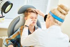 Medico femminile della gola OTORINOLARINGOIATRICA del naso dell'orecchio al naso d'esame della ragazza del lavoro Fotografia Stock