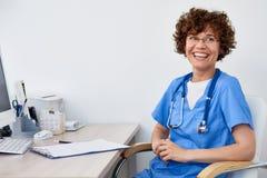 Medico femminile di risata allo scrittorio in ufficio fotografia stock libera da diritti