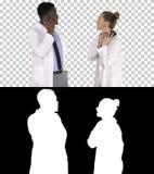 Medico femminile e maschio facendo uso dei telefoni cellulari che fanno le chiamate che dicono le notizie felici, Alpha Channel fotografia stock