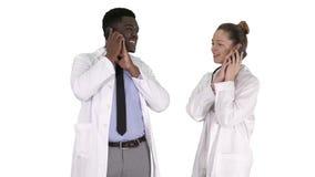 Medico femminile e maschio facendo uso dei telefoni cellulari che fanno le chiamate che dicono le notizie felici sul fondo bianco video d archivio
