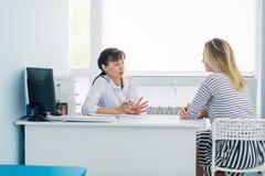 Medico femminile e paziente che parlano nell'ufficio dell'ospedale Sanità e servizio del cliente nella medicina fotografia stock libera da diritti