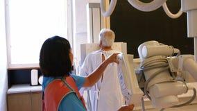Medico femminile ha installato la macchina per fare i raggi x di una spina dorsale dei pazienti stock footage