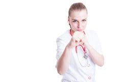 Medico femminile nervoso ed arrabbiato che sta in una posizione di pugilato fotografia stock