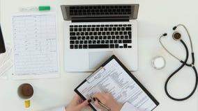 Medico femminile passa compilare il modulo di anamnesi Fotografie Stock Libere da Diritti