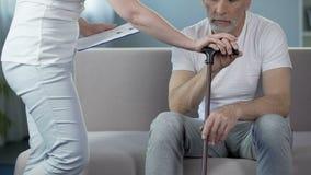 Medico femminile preoccupantesi che riempie annotazione clinica, pensionato maschio sostenente, clinica video d archivio