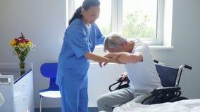 Medico femminile professionista che aiuta il suo paziente a sedersi nella sedia a rotelle archivi video
