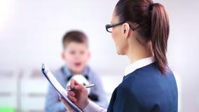 Medico femminile professionista dello psicologo infantile del primo piano medio che discute con il ragazzo e che fa le note archivi video