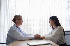 Medico femminile senior che parla e che conforta giovane PA asiatico della donna immagine stock